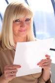 Middleaged businesswoman with sheet of paper — Stock fotografie