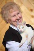 Smiling aged woman with cat on hands — Stock Photo