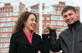 Young couple with key against many-storeyed house — Stock Photo