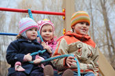 Three children on playground hold on rope — Stock Photo
