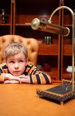 Pojken sitter på lyxiga kontor — Stockfoto