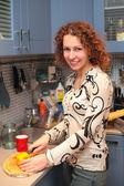 Jonge vrouw cuts paprika op keuken — Stockfoto