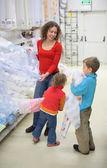 Jovem mulher com crianças em loja de têxteis — Foto Stock