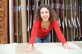 Jovem mulher na loja com tapete macio — Foto Stock