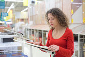 Young woman in shop chooses ceramic tile — Stock Photo