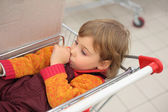 Little girl in shop lies in cart and holds finger in mouth — Stock Photo