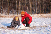 Mother plays with son in wood in winter — Stock Photo