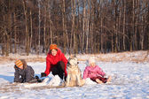 Mother with children and dog in wood in winter — Stock Photo