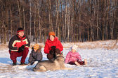 Parents with children and dog in wood in winter — Photo