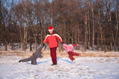 Father rotate children in wood in winter — Stock Photo