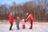 Parents and children in red huts play in wood in winter — Stock Photo
