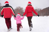 Parents with child run in park in winter from back — Stock Photo