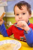 Little boy eats in kindergarten — Stock Photo