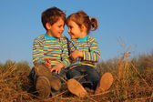 Two children in striped T-shirts sit on dry grass — Stock Photo