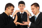 Three young businessmen do house from palms — Stock Photo