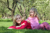 Daughter has leant elbows on mother lying on grass in park — Stock Photo