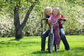 Girl with mother sit on bicycle in blossoming spring garden — Stock Photo