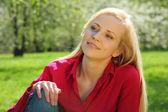 Hermosa rubia se sienta sobre césped en el parque en primavera — Foto de Stock