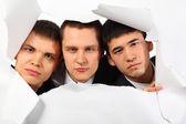 紙の穴で外を見て 3 つの若い男性 — ストック写真