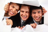 Tres jóvenes sonrientes mirando en el agujero en el papel de los hombres — Foto de Stock