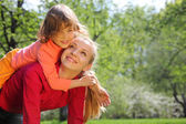 Daughter lies at mother on back in spring park — Stock Photo