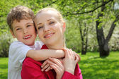 Son embraces behind mother for neck in park in spring — Stock Photo