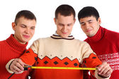 Three young men look on tape measure — ストック写真
