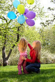 Mother with daughter with sheaf of balloons in garden in spring — 图库照片