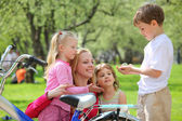 Mother with children and bicycle in park in spring — Stock Photo