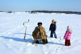 Two children and fisherman on frozen river — Stock Photo