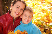 Mother and son in autumn wood — Stock Photo