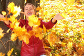 Girl throws yellow maple leaves — Stock Photo