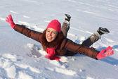 Mujer joven belleza yace en la nieve — Foto de Stock