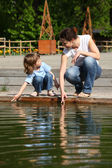 Mother with daughter in park at pool touch water — Stock Photo