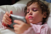 Little girl in bed with hendheld computer — Stock Photo