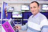 Elderly man in shop at information screen — Foto de Stock