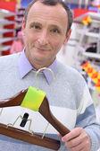 Homem idoso na loja com cabide para roupas nas mãos — Foto Stock
