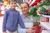Elderly man with boy in shop with plant in pot — Stock Photo