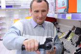 Homem idoso na loja com broca em mãos — Foto Stock