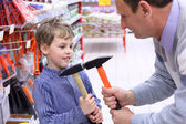 Elderly man with boy in shop with hammers in hands — Stock fotografie