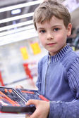 Boy in shop with tool set in hands — Stock Photo