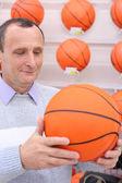 Anciano en tienda con pelota de baloncesto en las manos — Foto de Stock
