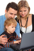 Parents whit son look on notebook — Stock Photo