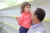 Elderly man at empty shelves in shop with child on hands — Stock Photo