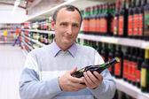 äldre man i butik med vinflaska i händer — Stockfoto