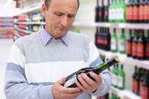Elderly man in shop looks on wine bottle in hands — 图库照片