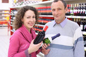 Gelukkig meisje en oudere man in winkel met wijn flessen in handen — Stockfoto
