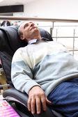 Osoby w podeszłym wieku człowiek leży w fotel masujący — Zdjęcie stockowe