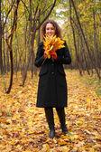 Mujer joven en el parque en otoño con las hojas amarillas — Foto de Stock