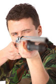 Man in camouflage pointed from gun — Stock Photo